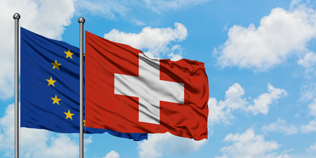 European Union and Switzerland flag waving in the wind against white cloudy blue sky together. Diplomacy concept, international relations.