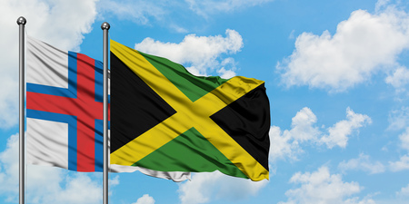 Faroe Islands and Jamaica flag waving in the wind against white cloudy blue sky together. Diplomacy concept, international relations. Stock Photo