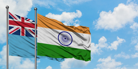 Fiji and India flag waving in the wind against white cloudy blue sky together. Diplomacy concept, international relations.