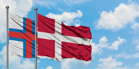 Faroe Islands and Denmark flag waving in the wind against white cloudy blue sky together. Diplomacy concept, international relations.
