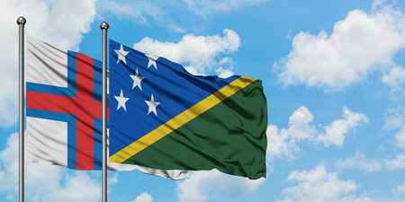 Faroe Islands and Solomon Islands flag waving in the wind against white cloudy blue sky together. Diplomacy concept, international relations. Stok Fotoğraf