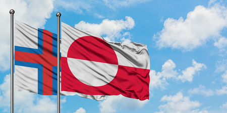Faroe Islands and Greenland flag waving in the wind against white cloudy blue sky together. Diplomacy concept, international relations.