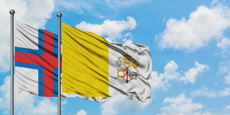 Faroe Islands and Vatican City flag waving in the wind against white cloudy blue sky together. Diplomacy concept, international relations.