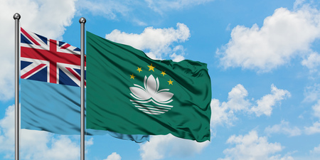 Fiji and Macao flag waving in the wind against white cloudy blue sky together. Diplomacy concept, international relations. Reklamní fotografie