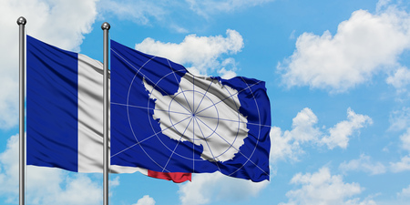 France and Antarctica flag waving in the wind against white cloudy blue sky together. Diplomacy concept, international relations. Stockfoto