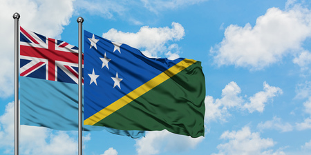 Fiji and Solomon Islands flag waving in the wind against white cloudy blue sky together. Diplomacy concept, international relations.