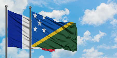 France and Solomon Islands flag waving in the wind against white cloudy blue sky together. Diplomacy concept, international relations.