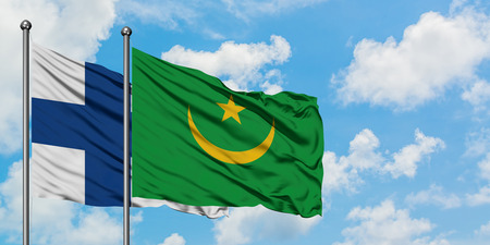 Finland and Mauritania flag waving in the wind against white cloudy blue sky together. Diplomacy concept, international relations.