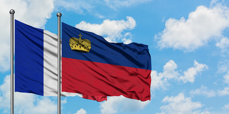 France and Liechtenstein flag waving in the wind against white cloudy blue sky together. Diplomacy concept, international relations.