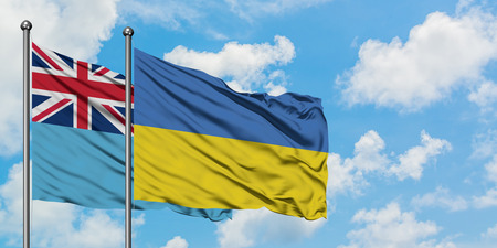 Fiji and Ukraine flag waving in the wind against white cloudy blue sky together. Diplomacy concept, international relations.