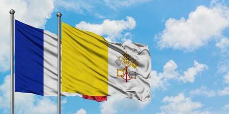 France and Vatican City flag waving in the wind against white cloudy blue sky together. Diplomacy concept, international relations.