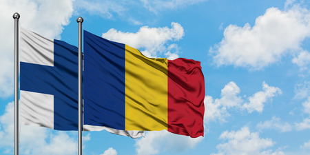 Finland and Romania flag waving in the wind against white cloudy blue sky together. Diplomacy concept, international relations.