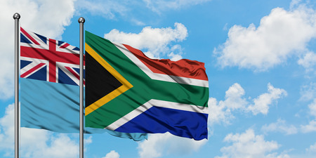 Fiji and South Africa flag waving in the wind against white cloudy blue sky together. Diplomacy concept, international relations.