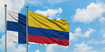 Finland and Colombia flag waving in the wind against white cloudy blue sky together. Diplomacy concept, international relations.