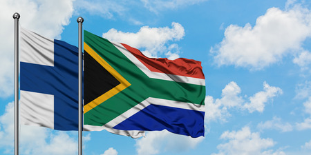 Finland and South Africa flag waving in the wind against white cloudy blue sky together. Diplomacy concept, international relations.