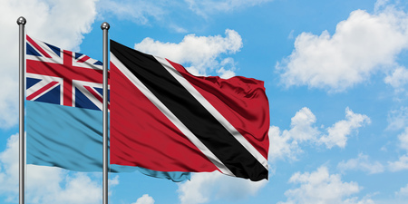 Fiji and Trinidad And Tobago flag waving in the wind against white cloudy blue sky together. Diplomacy concept, international relations. Stock Photo