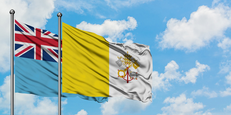 Fiji and Vatican City flag waving in the wind against white cloudy blue sky together. Diplomacy concept, international relations. 版權商用圖片