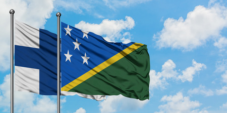 Finland and Solomon Islands flag waving in the wind against white cloudy blue sky together. Diplomacy concept, international relations.