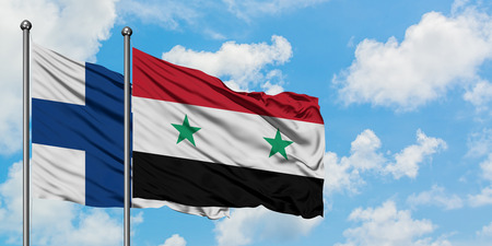 Finland and Syria flag waving in the wind against white cloudy blue sky together. Diplomacy concept, international relations.