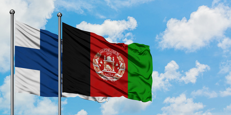 Finland and Afghanistan flag waving in the wind against white cloudy blue sky together. Diplomacy concept, international relations.