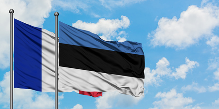 France and Estonia flag waving in the wind against white cloudy blue sky together. Diplomacy concept, international relations.
