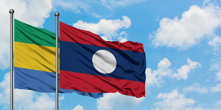 Gabon and Laos flag waving in the wind against white cloudy blue sky together. Diplomacy concept, international relations.