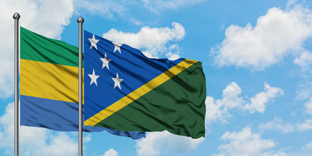 Gabon and Solomon Islands flag waving in the wind against white cloudy blue sky together. Diplomacy concept, international relations.