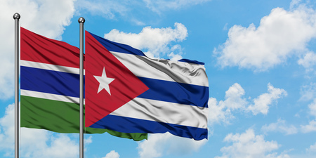 Gambia and Cuba flag waving in the wind against white cloudy blue sky together. Diplomacy concept, international relations.