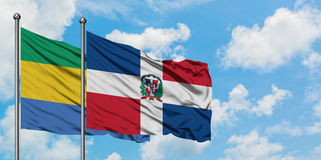 Gabon and Dominican Republic flag waving in the wind against white cloudy blue sky together. Diplomacy concept, international relations. 写真素材