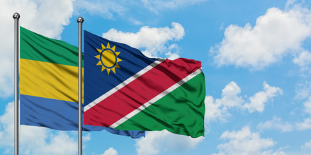 Gabon and Namibia flag waving in the wind against white cloudy blue sky together. Diplomacy concept, international relations.
