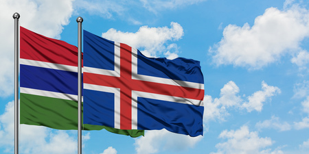 Gambia and Iceland flag waving in the wind against white cloudy blue sky together. Diplomacy concept, international relations.