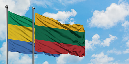 Gabon and Lithuania flag waving in the wind against white cloudy blue sky together. Diplomacy concept, international relations. Фото со стока