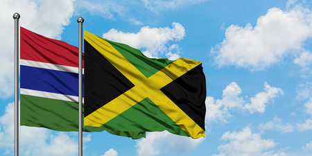 Gambia and Jamaica flag waving in the wind against white cloudy blue sky together. Diplomacy concept, international relations.