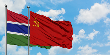 Gambia and Soviet Union flag waving in the wind against white cloudy blue sky together. Diplomacy concept, international relations.