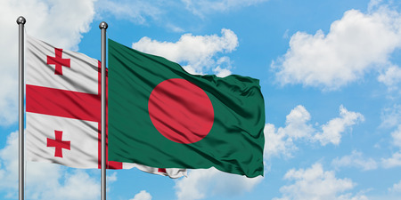 Georgia and Bangladesh flag waving in the wind against white cloudy blue sky together. Diplomacy concept, international relations. Stock Photo