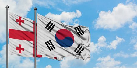 Georgia and South Korea flag waving in the wind against white cloudy blue sky together. Diplomacy concept, international relations.