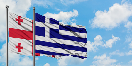 Georgia and Greece flag waving in the wind against white cloudy blue sky together. Diplomacy concept, international relations.