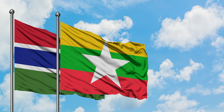 Gambia and Myanmar flag waving in the wind against white cloudy blue sky together. Diplomacy concept, international relations.