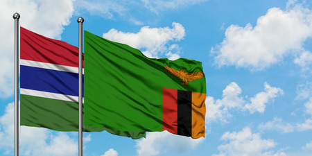 Gambia and Zambia flag waving in the wind against white cloudy blue sky together. Diplomacy concept, international relations. Stock Photo