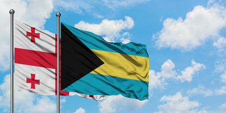 Georgia and Bahamas flag waving in the wind against white cloudy blue sky together. Diplomacy concept, international relations. Stock Photo - 123555625