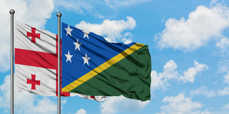 Georgia and Solomon Islands flag waving in the wind against white cloudy blue sky together. Diplomacy concept, international relations. Stok Fotoğraf