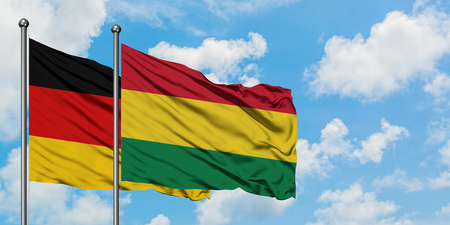 Germany and Bolivia flag waving in the wind against white cloudy blue sky together. Diplomacy concept, international relations. 免版税图像
