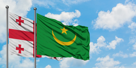 Georgia and Mauritania flag waving in the wind against white cloudy blue sky together. Diplomacy concept, international relations.