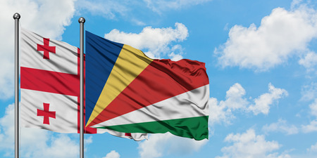 Georgia and Seychelles flag waving in the wind against white cloudy blue sky together. Diplomacy concept, international relations.