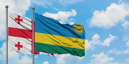 Georgia and Rwanda flag waving in the wind against white cloudy blue sky together. Diplomacy concept, international relations.