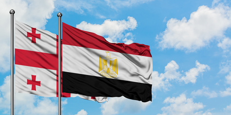 Georgia and Egypt flag waving in the wind against white cloudy blue sky together. Diplomacy concept, international relations.