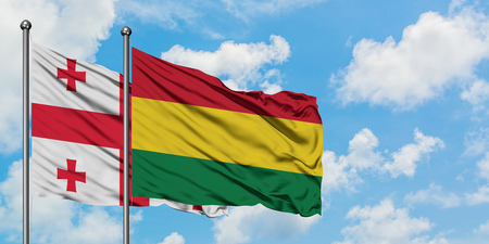 Georgia and Bolivia flag waving in the wind against white cloudy blue sky together. Diplomacy concept, international relations.