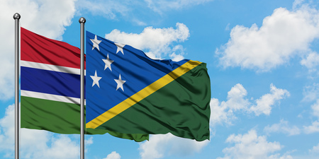 Gambia and Solomon Islands flag waving in the wind against white cloudy blue sky together. Diplomacy concept, international relations.