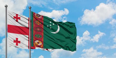 Georgien und Turkmenistan Fahnenschwingen im Wind gegen weißen bewölkten blauen Himmel zusammen. Diplomatie-Konzept, internationale Beziehungen.