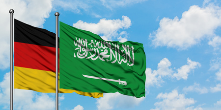 Germany and Saudi Arabia flag waving in the wind against white cloudy blue sky together. Diplomacy concept, international relations.
